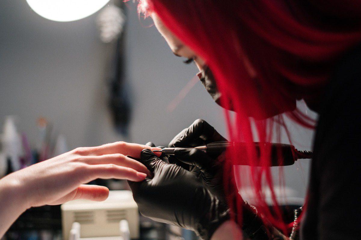 manos y esteticista realizando manicura a domicilio con instrumental